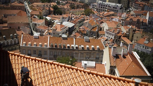 A painter works on the roof of a house Monday, Aug. 8, 2011, on a slope above Lisbon's Mouraria neigborhood, one of the city's oldest quarters. (AP Photo/Francisco Seco)